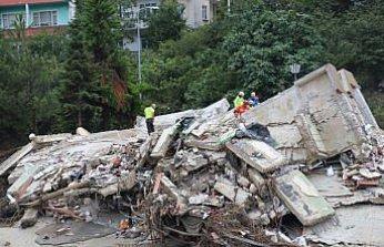 Sel nedeniyle yıkılan binanın altından yakınlarının sağ çıkmasını bekliyorlar